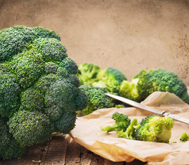 broccoli  in crumpled paper with knife,wooden background