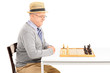 Man sitting at table and looking at a chessboard