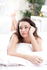 unhappy young woman lying in a bed