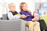 Mature couple eating popcorn and watching tv at home