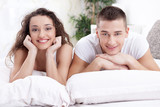 smiling young couple in love lying in bed