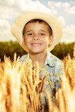 smiling young boy with straw hat in a field of wheat