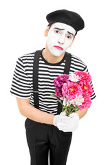 Sad mime artist holding a bouquet of flowers