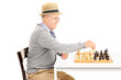 Senior playing a game of chess seated at table