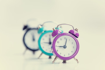 Three alarm clocks on white background.
