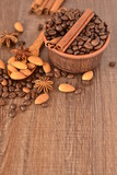 Coffee beans in a ceramic bowl and spices on wooden background