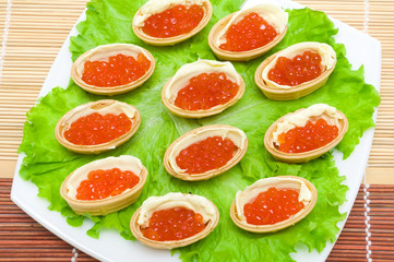 Tartlets with red caviar and butter on a plate