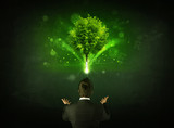 Businessman gesturing in front of a glowing tree