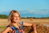 Beautiful woman   posing on a wheat bale