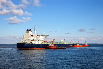 A huge oil tanker and three tugboats at work.