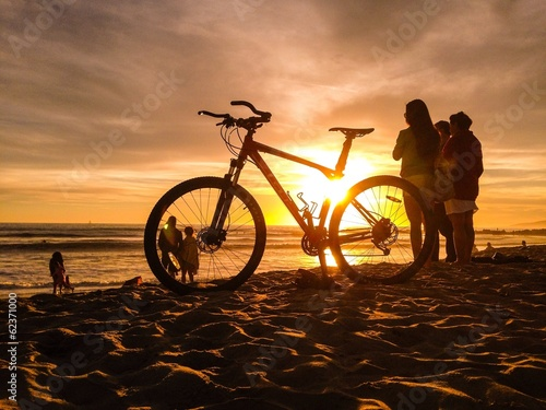 sunset sun shines through  bike on venice beach in los angeles