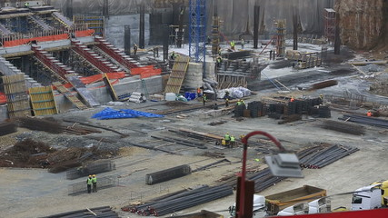 stadium construction zone with heavy equipment and workers