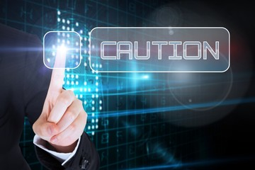 Businesswomans finger touching Caution button
