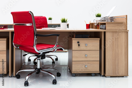 desks and red armchairs