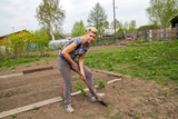 Smiling woman digs up beds in the garden