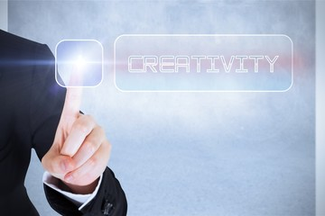 Businesswomans finger touching Creativity button