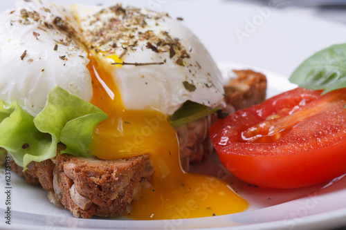 open poached egg, tomato and bread