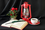 Open book, lamp and a cup of tea