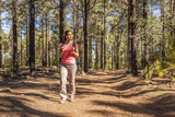 young woman hiking in a pine wood