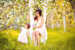 Happy woman and child in the blooming spring garden.Mothers day