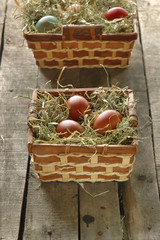 baskets with Easter eggs on old wooden table