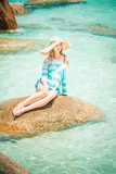 woman relaxing in hat on a stone in blue ocean