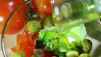 Olive oil flows in salad. Macro