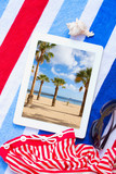 tablet on beach towels with sunbathing accessories