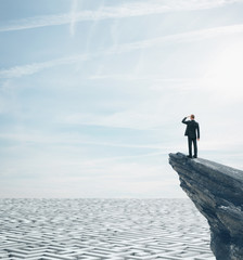 Businessman standing on a rock and looking at huge maze