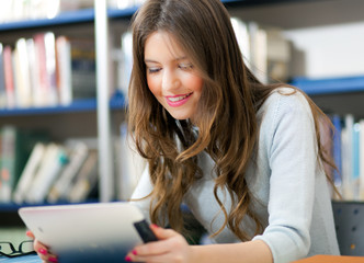 Female student using a tablet in a library