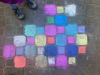 child chalk painting on the pavement