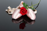 Two ballet slippers and red rose on black surface with spotlight