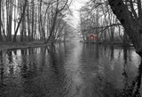 Monochromatic landscape of spring river with red house