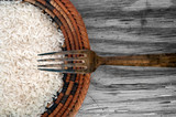 rice and fork on wood background texture