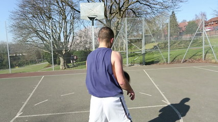 Basketball Player scoring a 3 point shot outdoors
