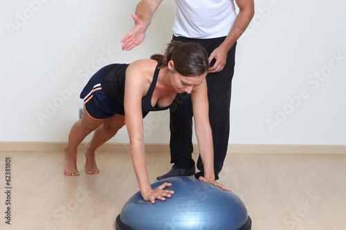 Frau macht Liegestütze auf Balancetrainer