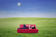 Asian female lying on red sofa with touchpad under lamp outdoor