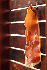 piece of serrano ham jamon Cured Meat hanged on hook