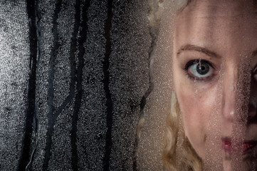 sad woman looking through window condensation