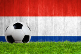 Soccer ball on grass with Netherlands flag background