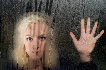 sad woman looking through condensation window