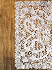 old wooden background with white lace napkin