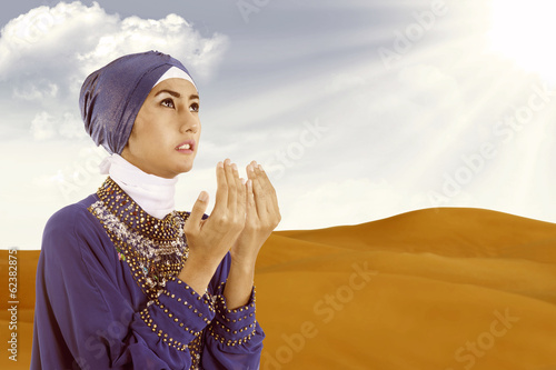 Beautiful female muslim praying in blue at desert
