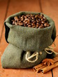Still life of coffee beans in canvas sack on wooden background