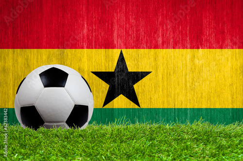 Soccer ball on grass with Ghana flag background