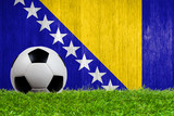 Soccer ball on grass with Bosnia and Herzegovina flag background