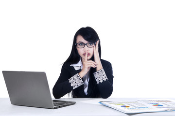 Businesswoman making silence gesture