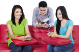 Three teenagers typing sms