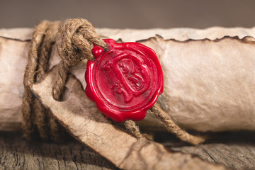 Old scroll paper on wooden background. Close up of wax seal.