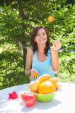 Happy Smiling Young Woman Juggling Oranges at her Garden